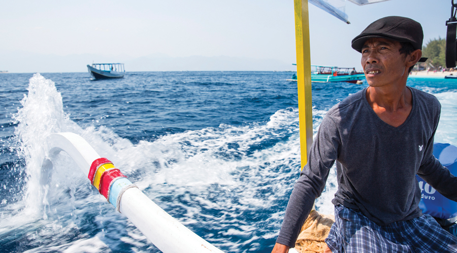 Fisherman steering boat at sea, Gili Meno, Lombok, Indonesia